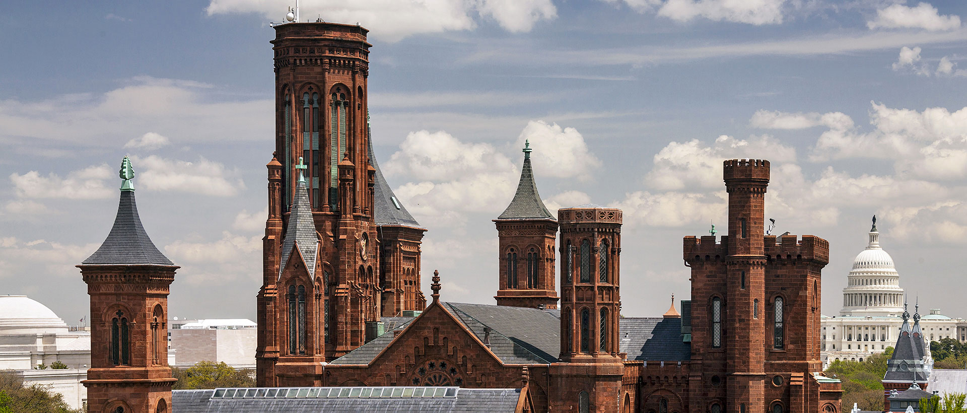 The smithsonian castle with the capitol in the background
