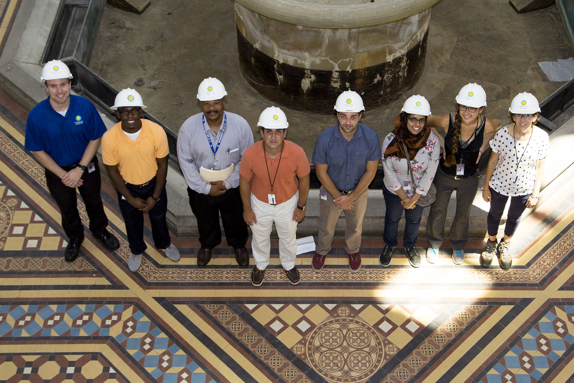 OFMR Interns pose for a photo with hard hats in the Arts and Industries Building